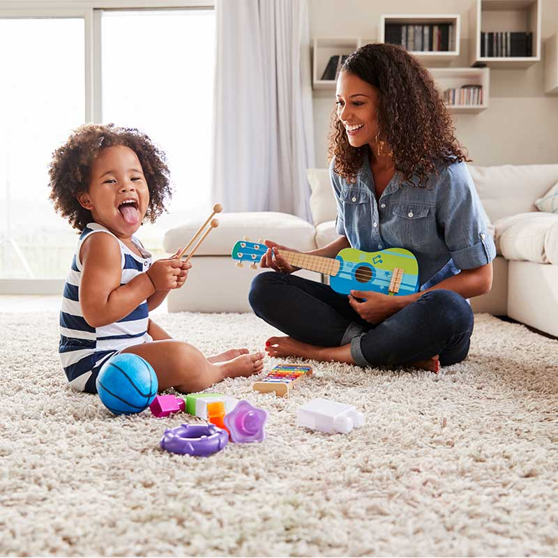 Afro-American Mother and Daughter Playing with Musical Instruments in the House