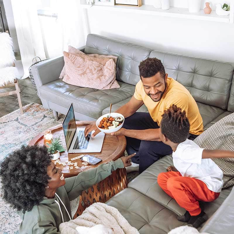 Afro-American Family Laughing and Playing on the Couch while Eating a Salad