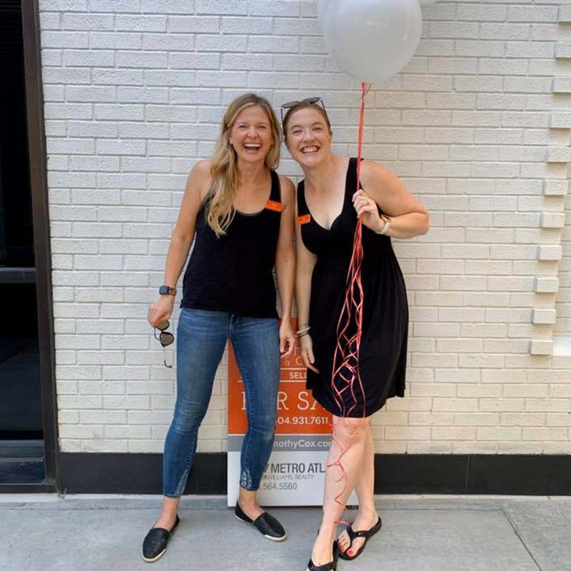 Portrait of Smiling Women Holding a Balloon in Front of a White Brick Walln
